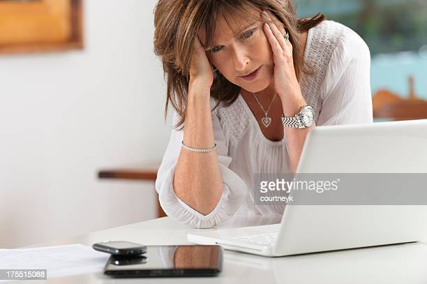 worried mature woman with technology - 40 49 jaar stockfoto's en -beelden