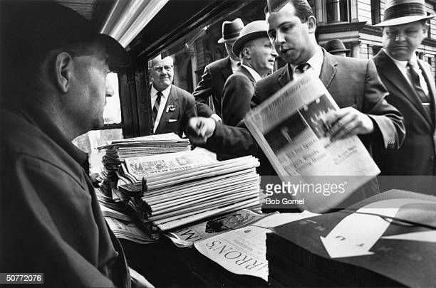 Worried men buying newspapers at a Wall Street newstand during stock market slump