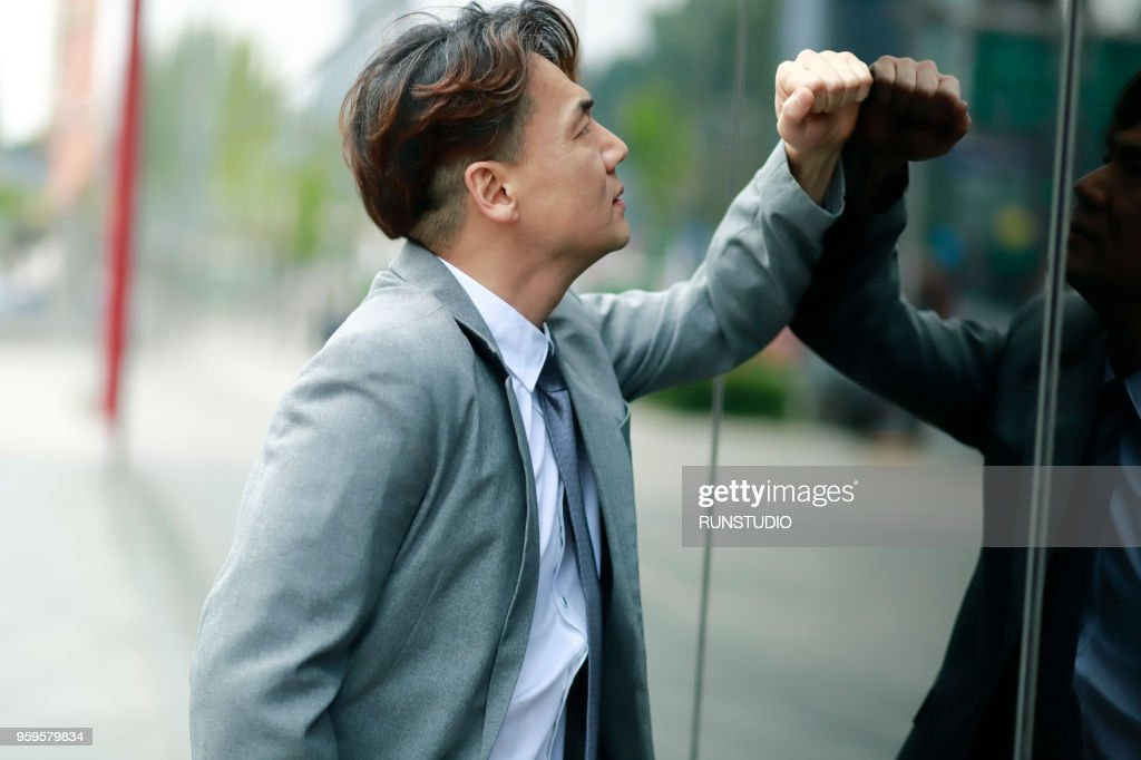 Worried Middle aged businessman leaning wall : Stock-Foto