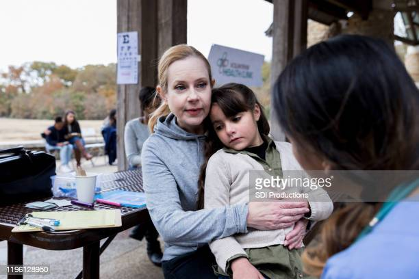 worried mom takes ill daughter to free clinic - free of charge stock pictures, royalty-free photos & images