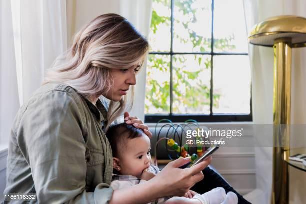 worried mom with sick baby scrolls through information on phone - estado médico imagens e fotografias de stock