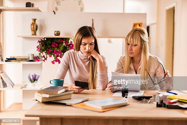 Worried mother and daughter calculating financial reports together.