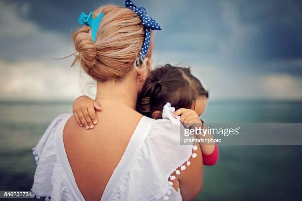 Mère inquiète est étreindre son petit bébé et à la recherche de l'orage qui s'annonce sur l'océan