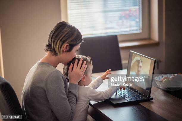worried mother kissing toddler head during his video call with separated father - divorce kids stock pictures, royalty-free photos & images
