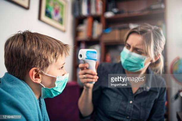 worried mother taking temperature of her sick son - infrared thermometer stock pictures, royalty-free photos & images