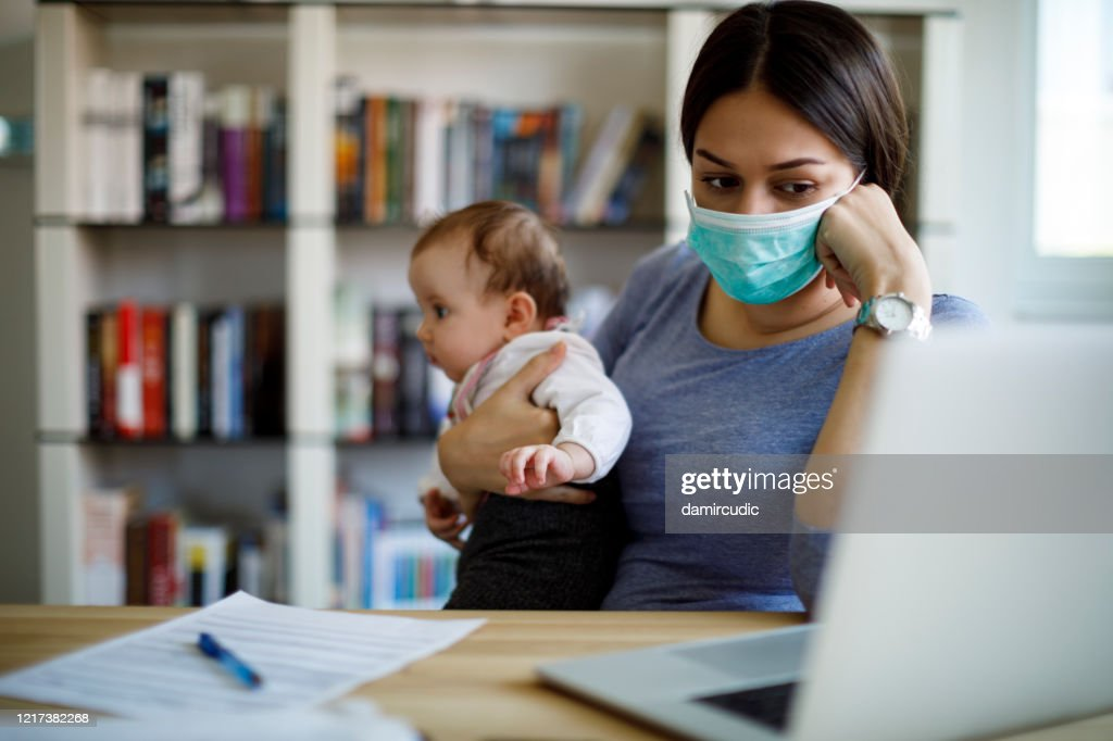 Worried mother with face protective mask working from home : Stock Photo