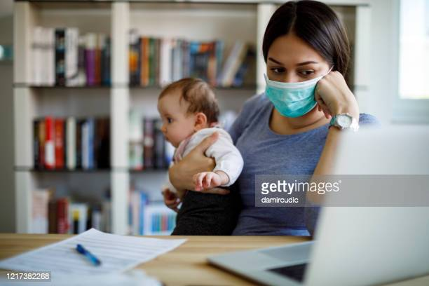 worried mother with face protective mask working from home - pandemic illness stock pictures, royalty-free photos & images