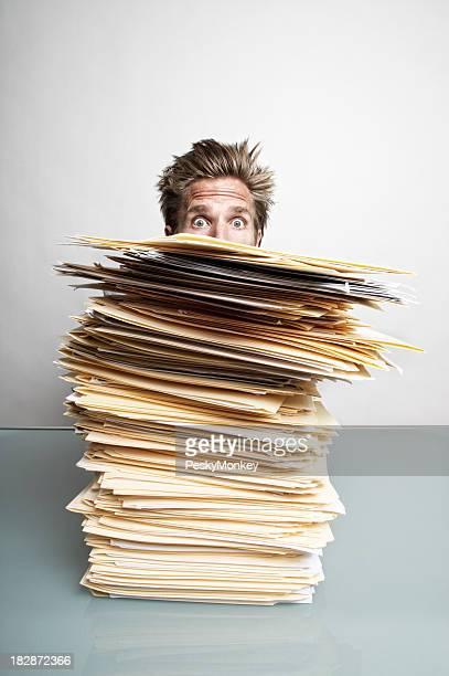 Besorgt Büroberuf Geschäftsmann Spähen über Papierkram auf dem Schreibtisch