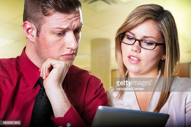 Worried office worker looks at disappointing report shown by colleague