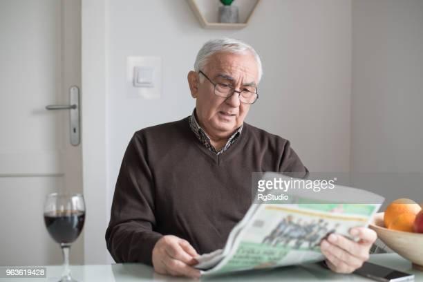 Besorgt alten Mann lesen Zeitungen
