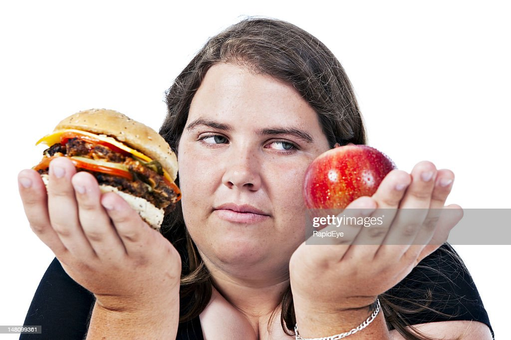 Worried overweight woman must choose between healthy and unhealthy foods : Stock Photo