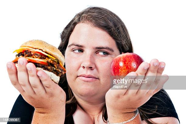 Worried overweight woman must choose between healthy and unhealthy foods