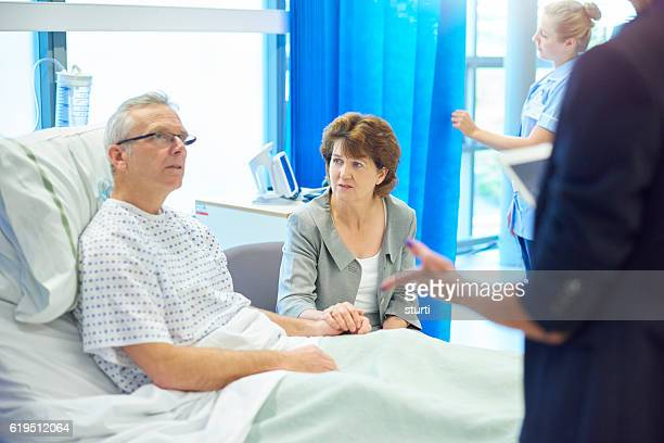 worried patient and wife chatting to doctor