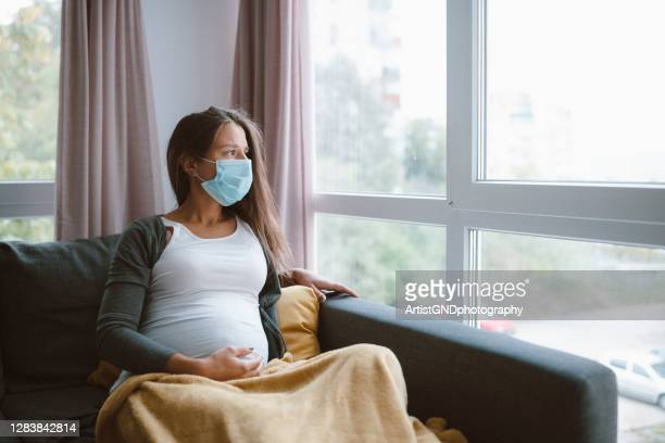 worried pregnant woman with protective face mask at home. - pregnant stock pictures, royalty-free photos & images