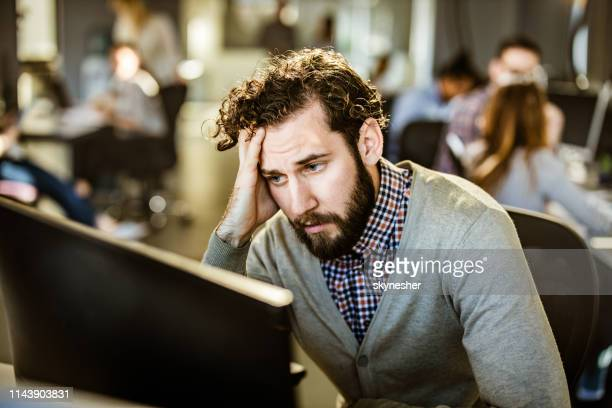 Worried programmer reading codes on desktop PC in the office.
