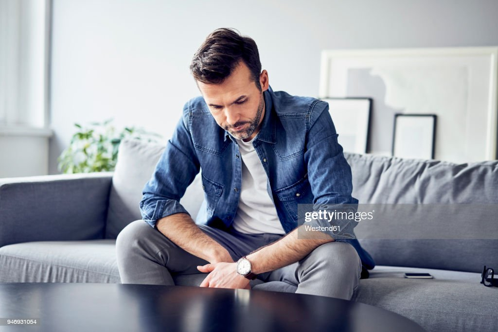 Worried sad man sitting on sofa : Stock Photo