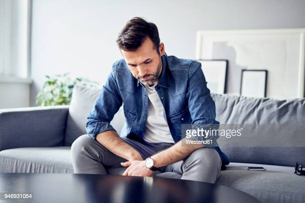 Worried sad man sitting on sofa