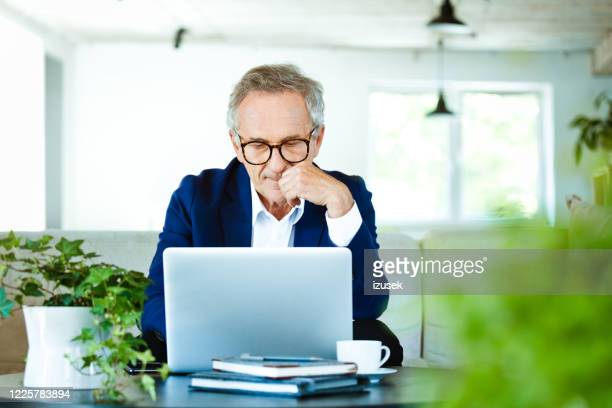 worried senior businessman working on laptop at home - using computer stock pictures, royalty-free photos & images