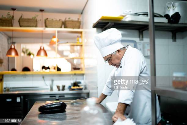 a worried senior chef in the kitchen counter - recession stock pictures, royalty-free photos & images