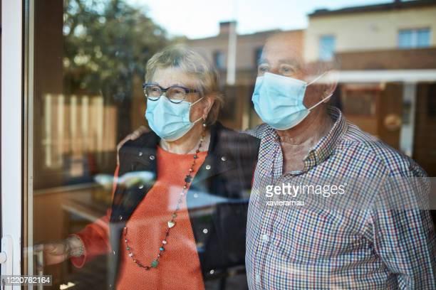 orolig äldre par tittar genom fönstret hemma i karantän - munskydd ensam bildbanksfoton och bilder
