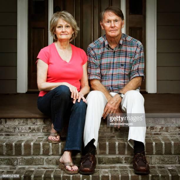 Älteres Paar sitzt vor Haus auf Schritt besorgt