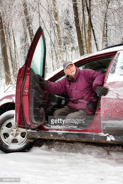 Worried senior man emerges from car during blizzard after accident
