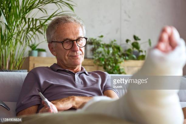 worried senior man with broken leg at home - injured stock pictures, royalty-free photos & images