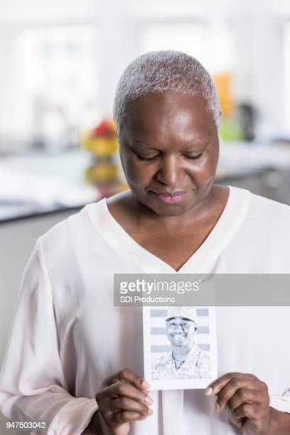 worried senior mom holds photo of soldier son - fallen soldier stock pictures, royalty-free photos & images