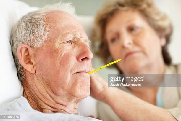 Worried senior woman comforting a sick elderly man