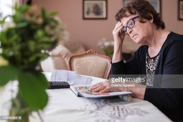 orolig äldre kvinna som håller pengar i händerna - fattigdom bildbanksfoton och bilder