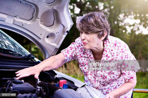 Worried senior woman reaches into engine of her broken-down car