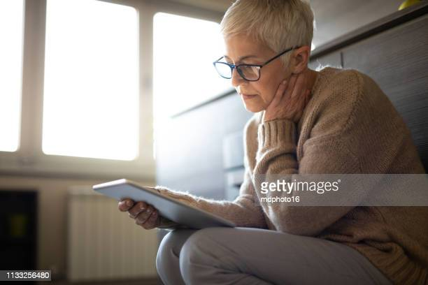 worried senior woman reading an e-mail on tablet - reflection stock pictures, royalty-free photos & images