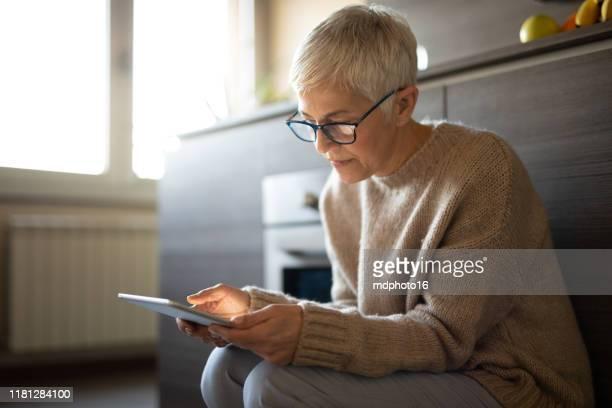 besorgte seniorin liest eine e-mail auf tablet - 60 64 jahre stock-fotos und bilder