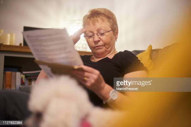 worried senior woman reading letter - grandma invoice stock pictures, royalty-free photos & images