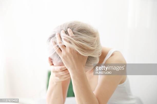 worried senior woman with hair loss - capelli grigi foto e immagini stock