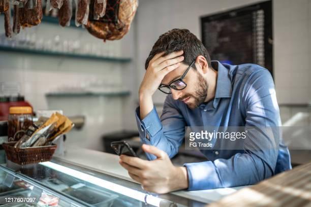 worried small business owner - falência imagens e fotografias de stock