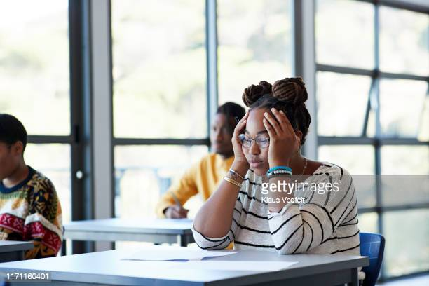 worried student sitting with head in hands at desk - bad student stock pictures, royalty-free photos & images