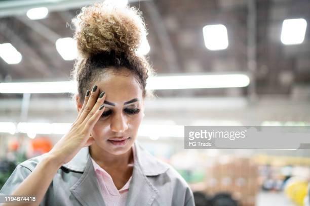 bezorgde technicus in de fabriek - opgestoken haar stockfoto's en -beelden