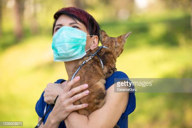 worried woman in face mask protectively carrying her devon rex cat on her shoulders outdoors - stock photo - cat face mask stock pictures, royalty-free photos & images