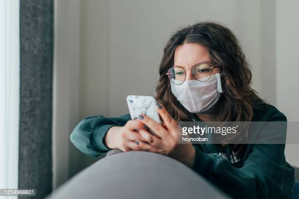 worried woman is reading news on phone - pandemic illness stock pictures, royalty-free photos & images