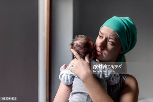 worried woman looking out the window with newborn baby in her arms - baby depression stock pictures, royalty-free photos & images