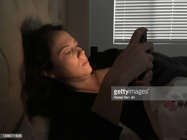 worried woman lying in bed using mobile phone - rafael ben ari fotografías e imágenes de stock