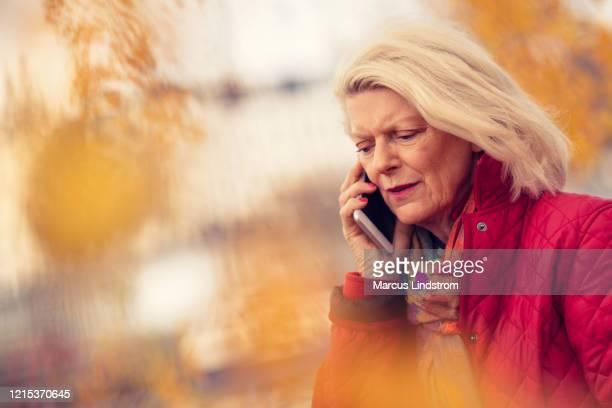 ongerust gemaakte vrouw op de telefoon - 65 69 jaar stockfoto's en -beelden