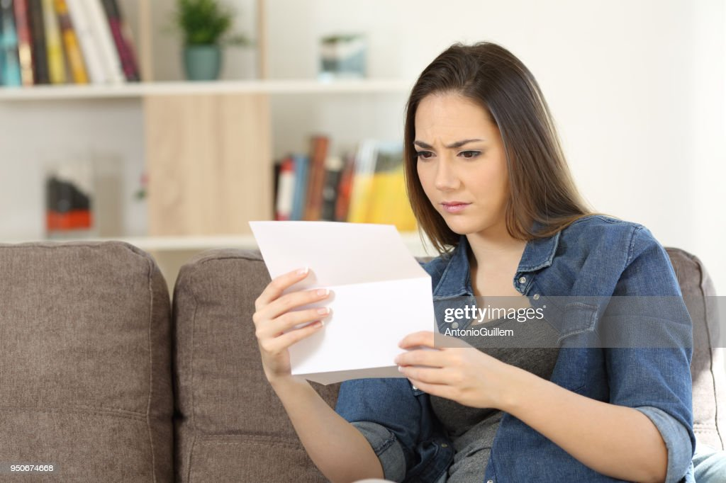 Worried woman reading a letter at home : Stock Photo