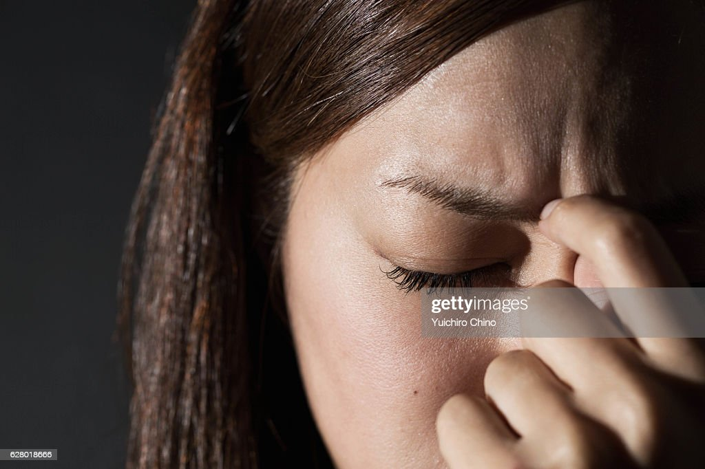 Worried woman rubbing her forehead : Stock Photo