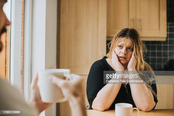 worried woman sits at a kitchen table holding her head in her hands - finance stock pictures, royalty-free photos & images