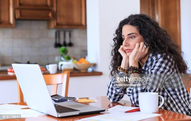 Worried woman sitting at home