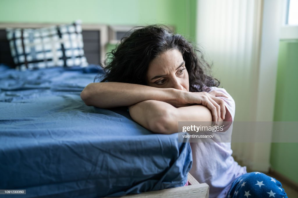 Worried woman sitting on floor next to bed : Stock Photo