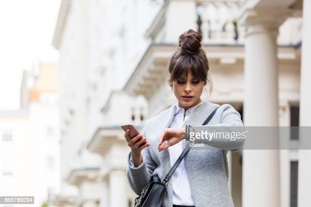 worried woman standing with smart phone in front of city house - istantanea foto e immagini stock