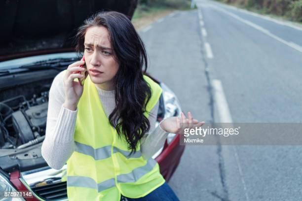 Besorgt Frau am Telefon neben ihr Auto zerlegt